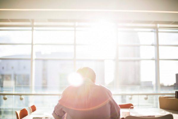 Ein Mitarbeiter im sonnigen Büro (Foto: Bethany Legg / Unsplash)